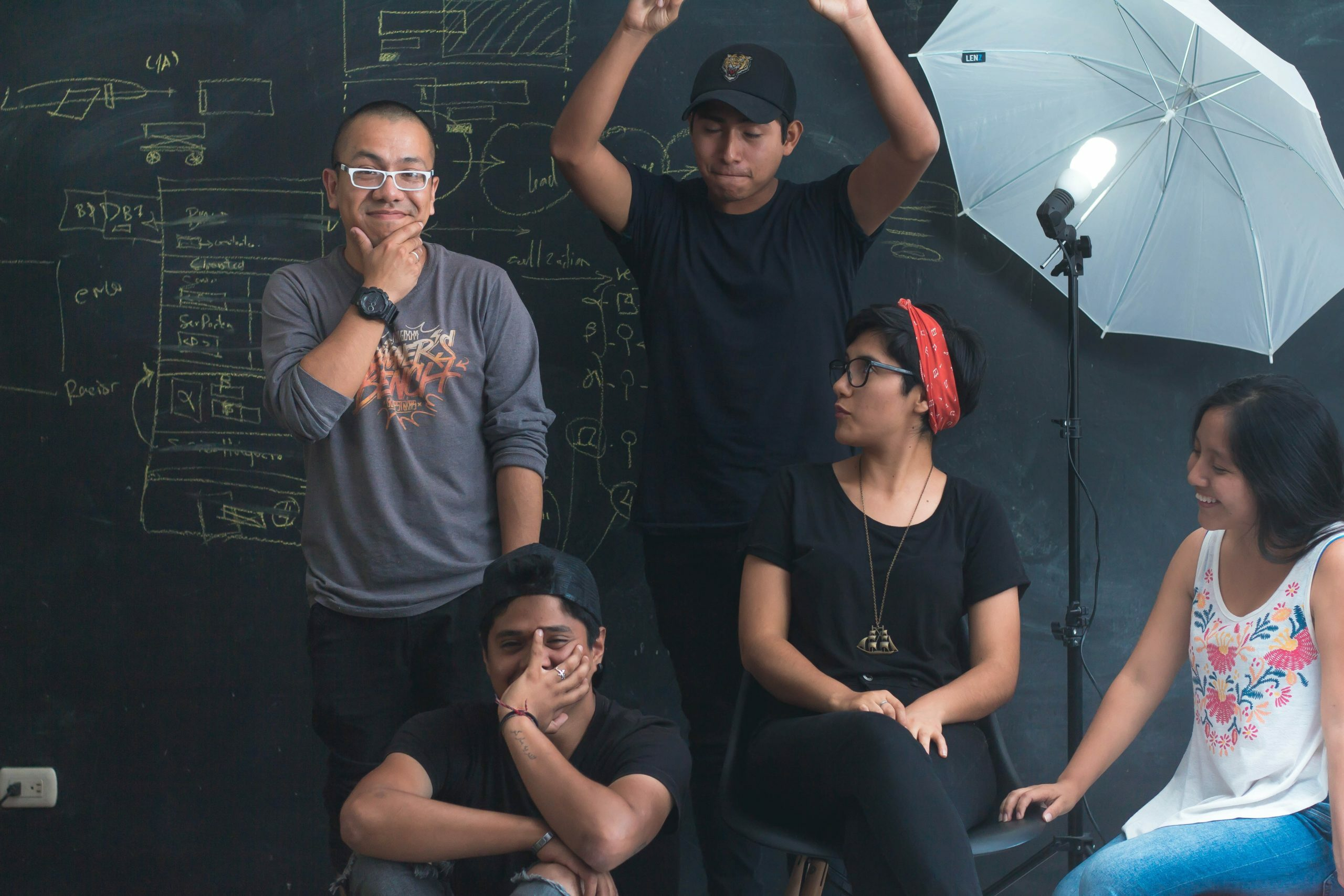 Five people posed in front of a chalkboard